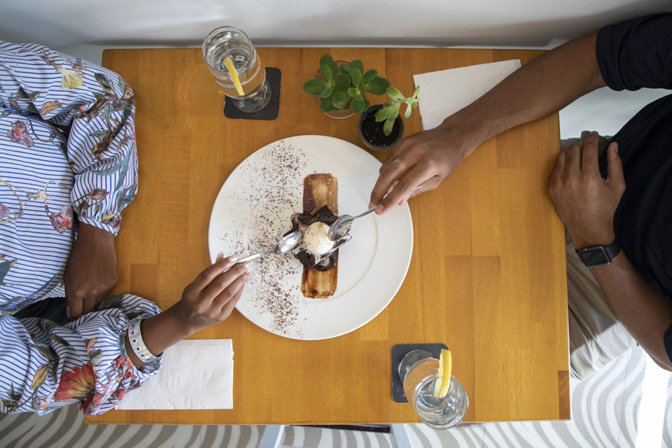 Two people share an artfully plated chocolate dessert