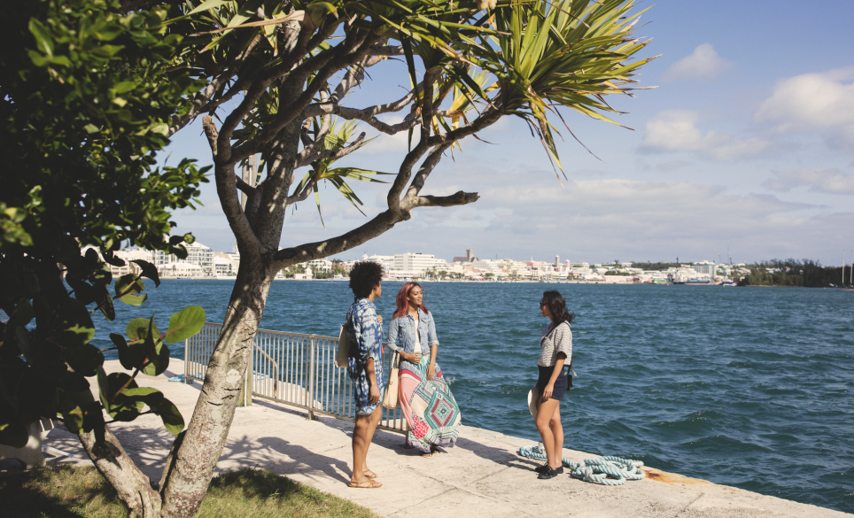 Three young women stand seaside on their annual girls trip in Bermuda