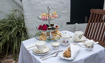 High-tea set on the table in the garden at Bermuda Perfumery