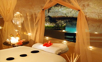 The view looking out of a luxurious spa tent onto clear water in a cave