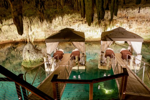 Massage tents over water inside a cave full of stalactites
