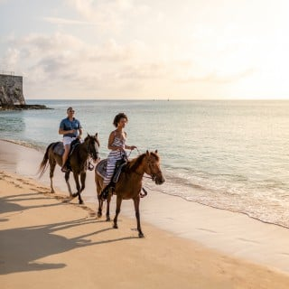 Couple horseback riding on beach