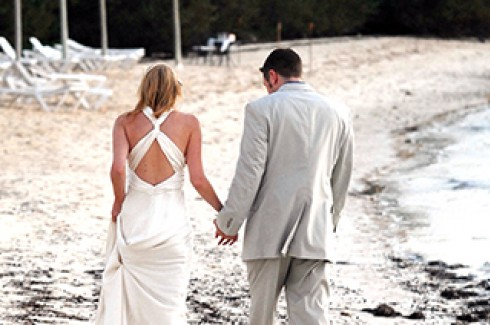 Couple walking down the beach in wedding attire at Cambridge Beaches Resort & Spa