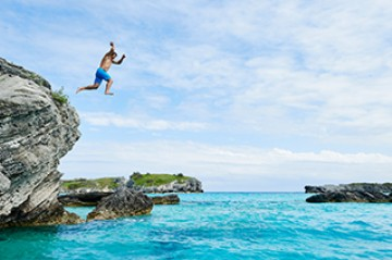 Man jumping off of a rock into the ocean