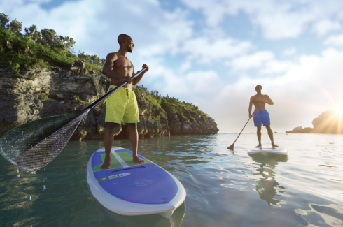 Two men enjoy stand-up paddleboarding on a sunny Bermuda day.