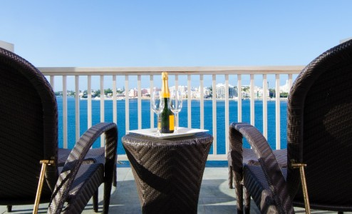 Champagne site on a table between two chairs overlooking Bermuda's Great Sound