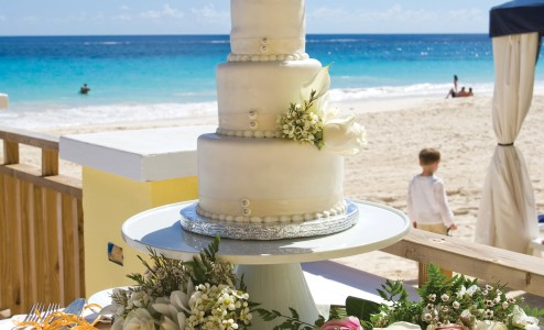 A wedding cake on a balcony looking over Elbow Beach